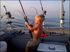 Tommy Spencer has a fish on the line during a trip on Lake Michigan.