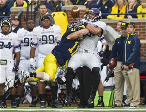 Michigan safety Jordan Kovacs breaks up a pass intended for Northwestern tight end Dan Vitale.