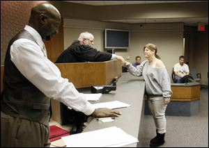Holly Most  shakes hands with Judge Brian MacKenzie, while Mike McGlown, probation officer, stands by at a session of  Veterans Court in Novi, Mich.