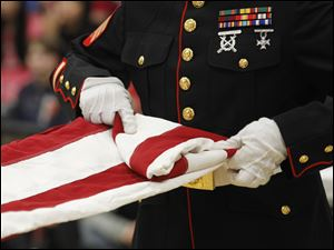 Weapons Co. 124 Marine Sgt. Shawn Campbell, folds a flag during a flag folding demonstration.