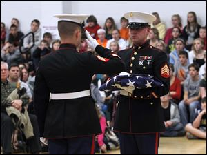 Weapons Co. 124 Marine Honor Guard Sgt. Jared Shaffer salutes  Shawn Campbell during a flag folding demonstration.