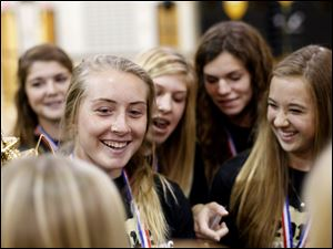 Maddy Williams, a senior, laughs while mingling with her teammates after a pep rally at Perrysburg High School.