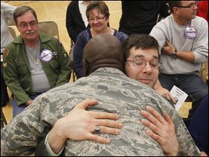 180th Fighter Wing chaplain Lt. Col. Harold Owens hugs Army veteran Matt Drake.