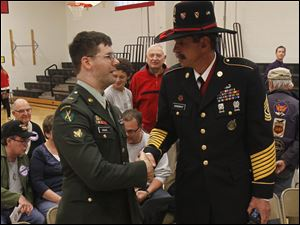Army veteran Spec. Matt Drake, left, shakes hands with retired Army First Sgt. Tim Gangway.