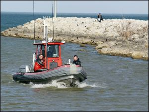 Jerusalem Township Fire Department members return to shore after searching for a boat that capsized on Maumee Bay that had two men on board Sunday.