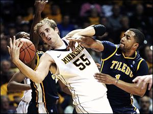 Minnesota's Elliot Eliason (55) loses control of the ball between Toledo's Dominique Buckley, right, and Rian Pearson, left, during the second half. The Gophers pounded UT 82-56.