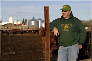 Doyle Johannes, who supports North Dakota constitutional amendment aimed at protecting the right to farm and ranch, stands next to his cattle feed lot on his farm in Underwood. N.D.