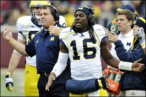 Michigan head coach Brady Hoke, left, and quarterback Denard Robinson, right, call over the offense during a timeout in the third quarter of an NCAA college football game against Minnesota, Saturday, Nov. 3, 2012, in Minneapolis. Robinson did not play because of an undisclosed injury.