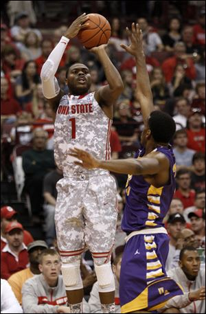 Ohio State's Deshaun Thomas, left, shoots over Albany's Jayson Guerrier during the Buckeyes' 82-60 victory Sunday in Columbus.