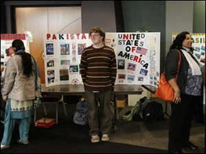 Zack Duane, of Bowling Green, center, set up the bulletin board representing the United States of America alongside boards created by international students.
