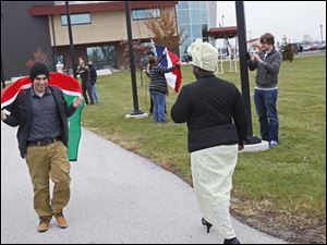 Jordanian student Moawiah Daramirih, left, carries his country's flag to its flag pole.