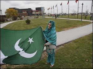 Pakistani student Razia Sultana laughs while she and another student raise her country's flag alongside students representing other nations from around the world.