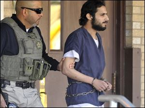 Khalid Ali-M Aldawsari, 22, right, is escorted from the federal courthouse in Amarillo, Texas by U.S. Marshals Tuesday.