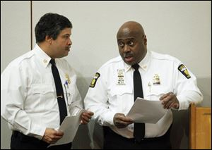 The Toledo Fire and Rescue chief, Luis Santiago, left, and Toledo Police Chief Derrick Diggs, right, attend the announcement for the proposed 2013 operating budget at One Government Center.
