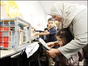 Khadiga Al-Jabri reads to Lena Balaa and Zachary Sayed after Books 4 Buddies donated materials to replace those lost in a recent arson at the Islamic Center of Greater Toledo.
