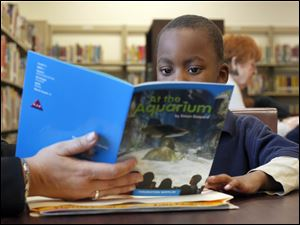 Ke'Mon Anderson shares a book about life at an aquarium with a tutor in the library of Pickett Elementary School. He is part of  the 'Creating Young Readers' program.