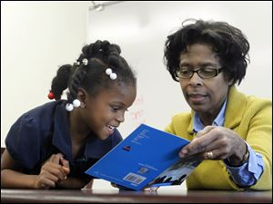 Volunteer reader Doris Whatley and Kanijah Edwards read in the library of Pickett Elementary School. They are using a technique in which they take turns reading a book.
