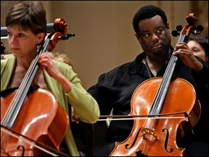 Cello players Martha Reikow, left, Damon Coleman, right, members of the Toledo Symphony (TSO), prepare during a rehearsal Saturday, May 7, 2011, for an evening performance at Carnegie Hall in New York. The performance will also include the Cold War-themed political play, Every Good Boy Deserves Favour as part of the program, with actors taking the stage with the TSO.