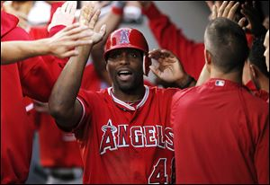Los Angeles Angels' Torii Hunter being congratulaed in the dugout during a baseball game against the Seattle Mariners in Seattle.