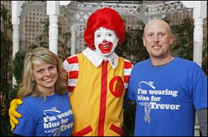 Jill and Nathan Bailey, of Defiance, pose for a photograph with Ronald McDonald during the the 4th Annual Heartwarming Party to benefit Ronald McDonald House Charities. The event, which drew hundreds of people, was held at the Hilton Garden Inn at Levis Commons in Perrysburg.