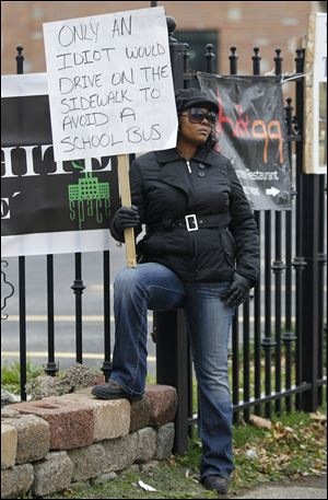 Shena Hardin holds up a sign as she serves a highly public sentence Wednesday in Cleveland.  Hardin drove on a sidewalk to avoid a Cleveland school bus that was unloading children.