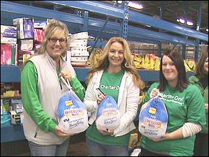 Charter One volunteers Laura Oros, Michelle Pommeranz, and Julie King load turkeys donated to the Toledo Northwestern Ohio Food Bank as part of Charter One's Carving Out Hunger program.