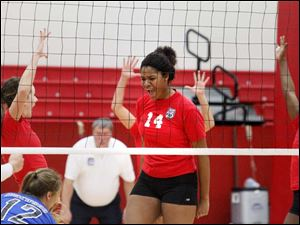 Owens Community Collge's freshman middle blocker Jazmine Thomas, center, cheers after securing a point.