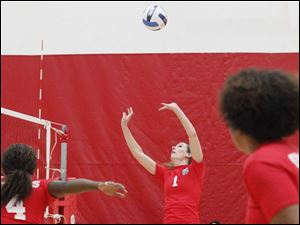 Owens Community College's sophomore setter Molly Hilfinger, center, sets up a spike.