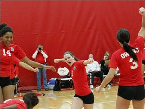 Owens Community College's freshman middle blocker Jazmine Thomas, left, sophomore setter Molly Hilfinger, center, and sophomore outside hitter Alyssa Meis, right, cheer after scoring the match winning point.