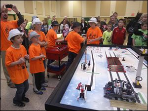 4th grader Seymen Ozbay, left, excitedly watches his robot peform.