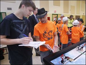 Lego competition judge Maxwell Paulun, of Southview High School, confers with coach Tod Losey.