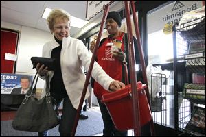 Carol Regnier donates money while volunteer Debra Vickers rings a bell during The Salvation Army's annual Red Kettle Drive kickoff at The Anderson's store in West Toledo.