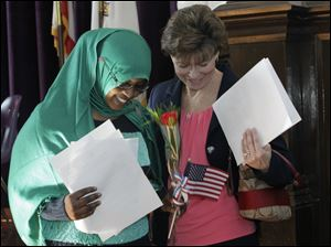 Fatuma Ibrahim Barqadle, of Somalia, left, is helped down the steps by Annie Crawford, federal court clerk.