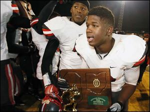 Central Catholic's Amir Edwards (20) runs with the Division II regional championship trophy.