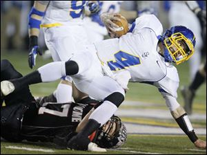 McComb High School player Dalton Auchmuty, 17, tackles Delphos St. John's player Mark Boggs during the first quarter at Donnell Stadium in Findlay.