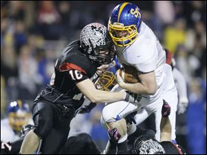 McComb High School player Mitch Schroder ,16, hits Delphos St. John's player Tyler Jettinghoff, 14.