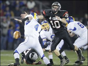 McComb High School player Clay Dysert, 10, pressures Delphos St. John's quarterback Mark Boggs, 4.
