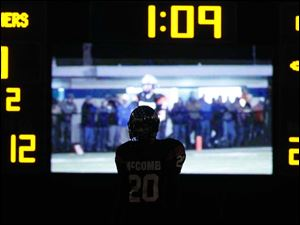 McComb High School player Clay Grubb, 20, is framed by the scoreboard as he awaits a punt against Delphos St. John's.