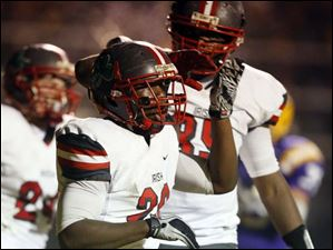 Central Catholic's Amir Edwards (20) celebrates scoring a touchdown.