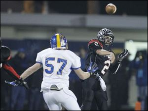 McComb High School quarterback Dalton Buck, 2, throws the ball over Delphos St. John's player Kody White, 57.