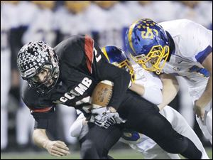 McComb High School player Dalton Buck, 2, is tackled by Delphos St. John's players Will Buettner, 81, and Cody Looser, 11.