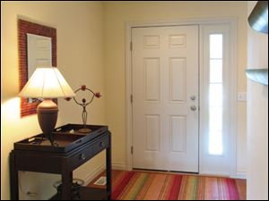 The model home's wide foyer welcomes visitors with beautiful oak hardwood floors.