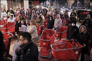 FILE- In this  Friday, Nov. 25, 2011, file photo, a crowd of shoppers wait outside the Target store in Lisbon, Conn., before the store opens for Black Friday shopping at midnight. Stores are making a big push to lure in bargain-hungry shoppers before the Friday after Thanksgiving, the traditional start of the holiday shopping season. They are putting on special sales that further creep into Turkey Day, and earlier.  (AP Photo/The Day, Sean D. Elliot, File)