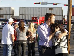Bystanders react as emergency personnel work the scene where a trailer carrying wounded veterans in a parade was struck by a train in Midland, Texas.