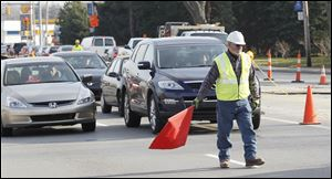 A worker stops traffic due to gas line construction Thursday on Monroe Street, between Secor Road and Sylvania Avenue.
