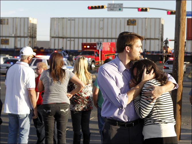 Veterans Parade-Train Bystanders react as emergency personnel work the scene where a trailer carrying wounded veterans in a parade was struck by a train in Midland, Texas.