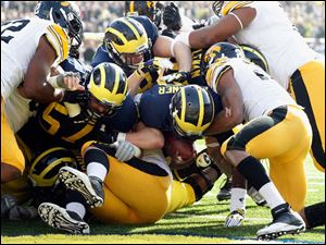 Michigan QB Devin Gardner (12) scores a touchdown against Iowa on a sneak during the first quarter.