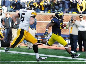 Michigan RB Vincent Smith scores a touchdown as Iowa's Tanner Miller (5) is too late to stop him.