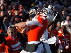 BGSU's Bart Tanski bobbles the ball for an incomplete pass near the end zone after pressure from Kent State's Norman Wolfe Jr.