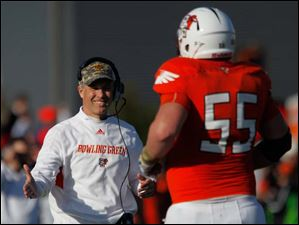 BGSU head coach Dave Clawson shakes hands with Alex Huettel after BGSU scored a touchdown.